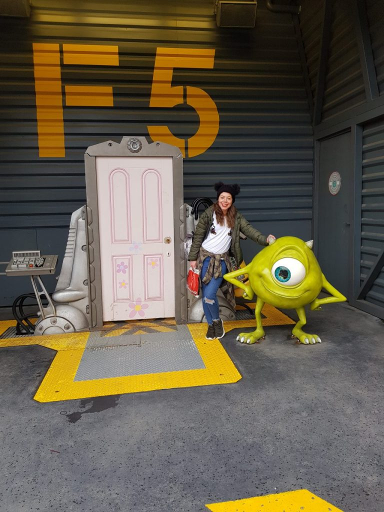 a white door from monsters inc with a small green monster (Mike Wazowski) and a girl in between