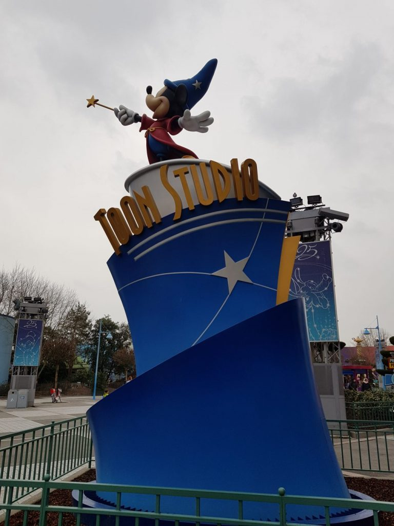 Statue of Mickey Mouse in wizards outfit from Fantasia. He reaches into the air with a yellow star wand, has a red gown on and blue starry wizards hat. He stands on a blue platform with Toon Studio written in gold.