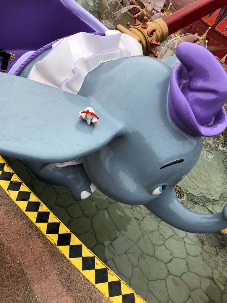 Dumbo tsum tsum on the Dumbo the flying elephant ride at Disneyland Paris. A grey plastic elephant wearing a purple hat and outfit