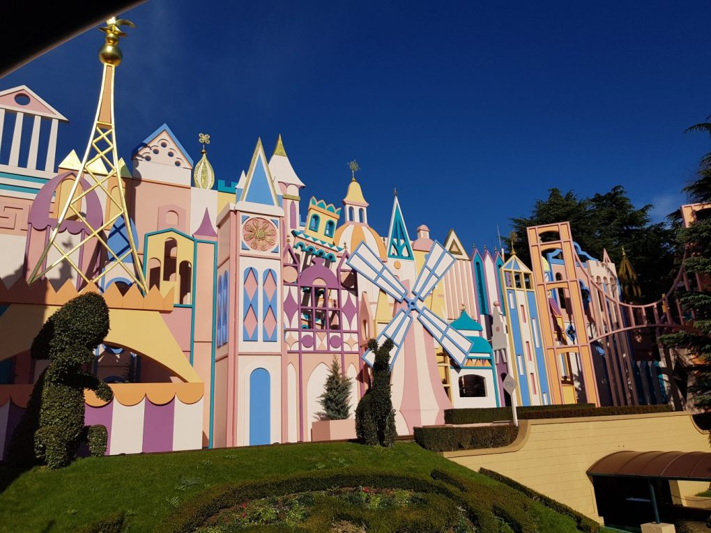 The outside of the It's a Small World ride at Disneyland Paris. A colourful, pastel coloured row of building like shapes with golden roofs