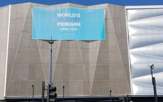 Outside shot of the World's largest Primark building. A grey angular building with a blue sign with white writing on it saying world's biggest Primark.