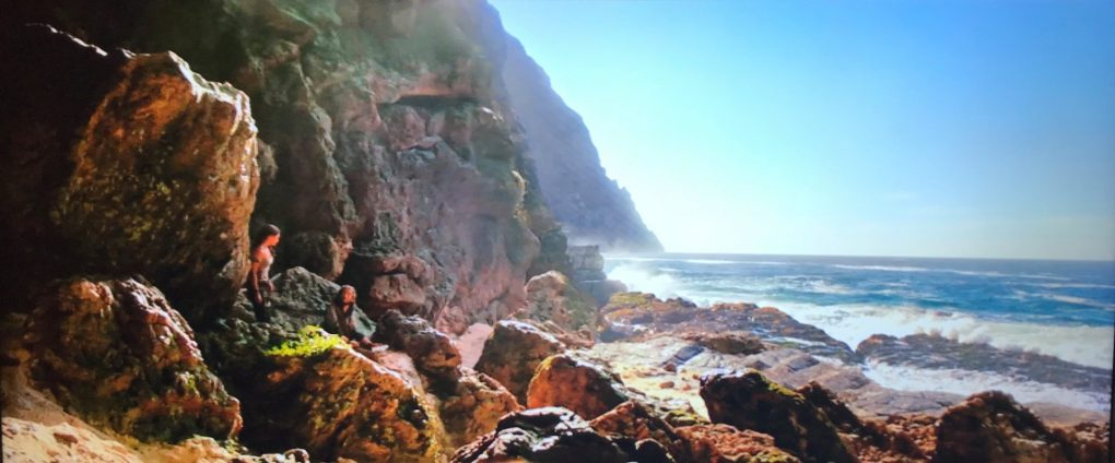 A scene from the Tomb Raider movie where Lara Croft is on a beach looking out over the sea