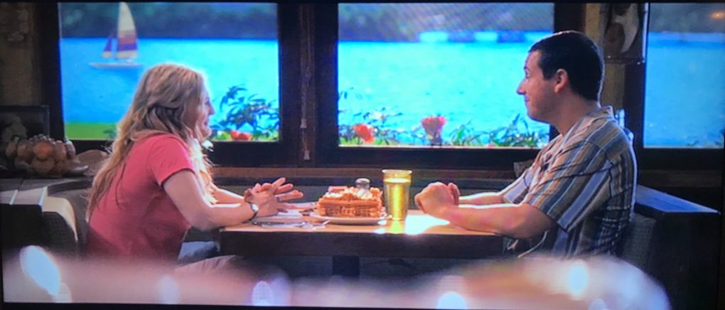 A scene from 50 first dates where a man and woman are sat in a restaurant across the table from each other with a large fishtank in the background