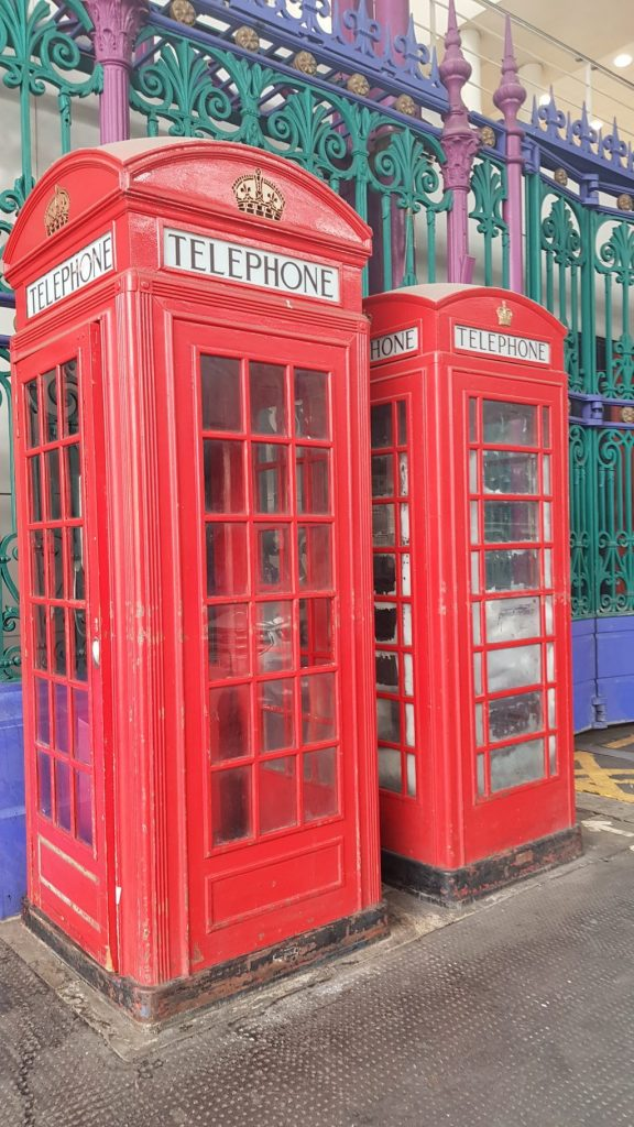 Red telephone boxes in front of a green fence found whilst on the Hidden City London trail