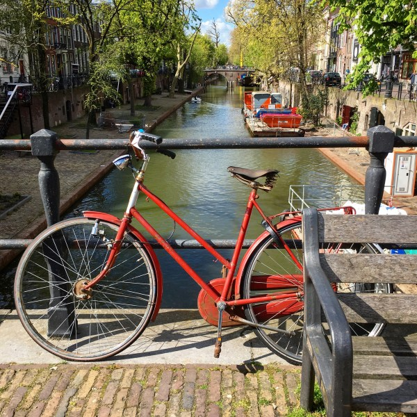Cute red bike with a bell and lights. Also a view of the canal | Biking in the Netherlands | Utrecht | The Travel Medley