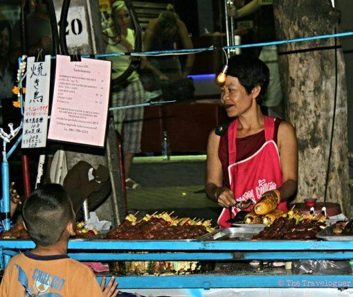 Boy waits for his corn, Bangkok street scene