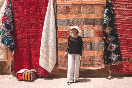 Jasmine stands in front of colourful woven rugs in Marrakech medina, Morocco