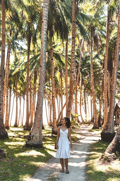 A lady in a white dress walks along a path lined with palm trees, Siargao
