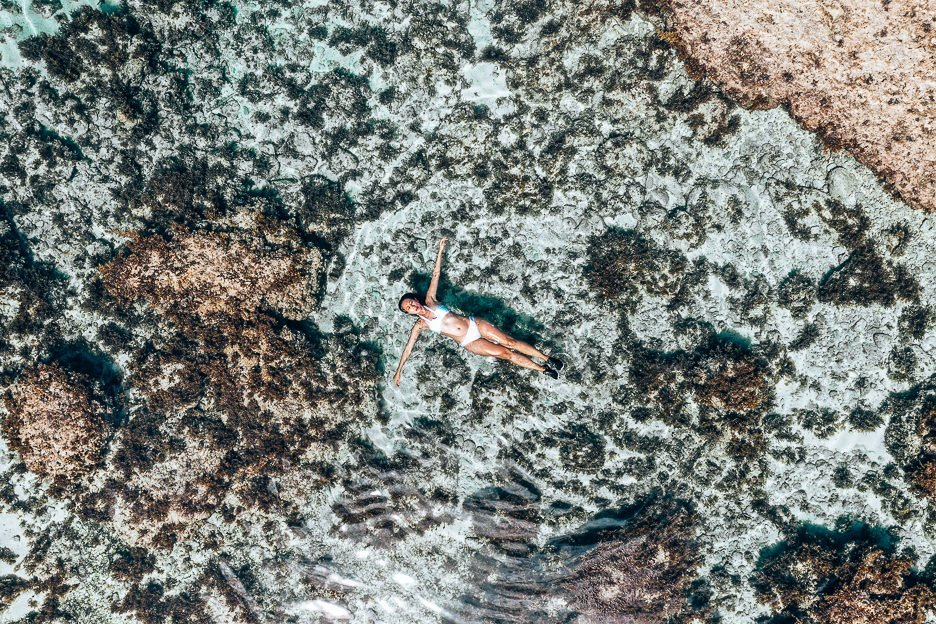 A girl in a white bikini floats on her back in a tidal pool at Magpupungko, Siargao