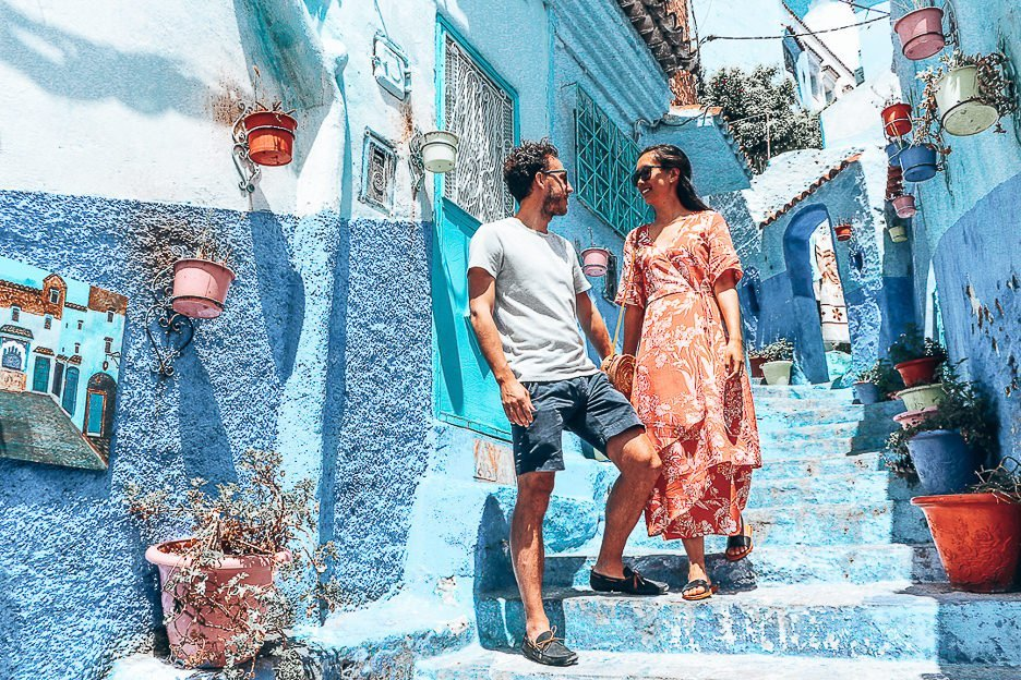 A couple stand on stairs among potted plants in Chefchaouen, Morocco - 5 Things When Dating Travelling