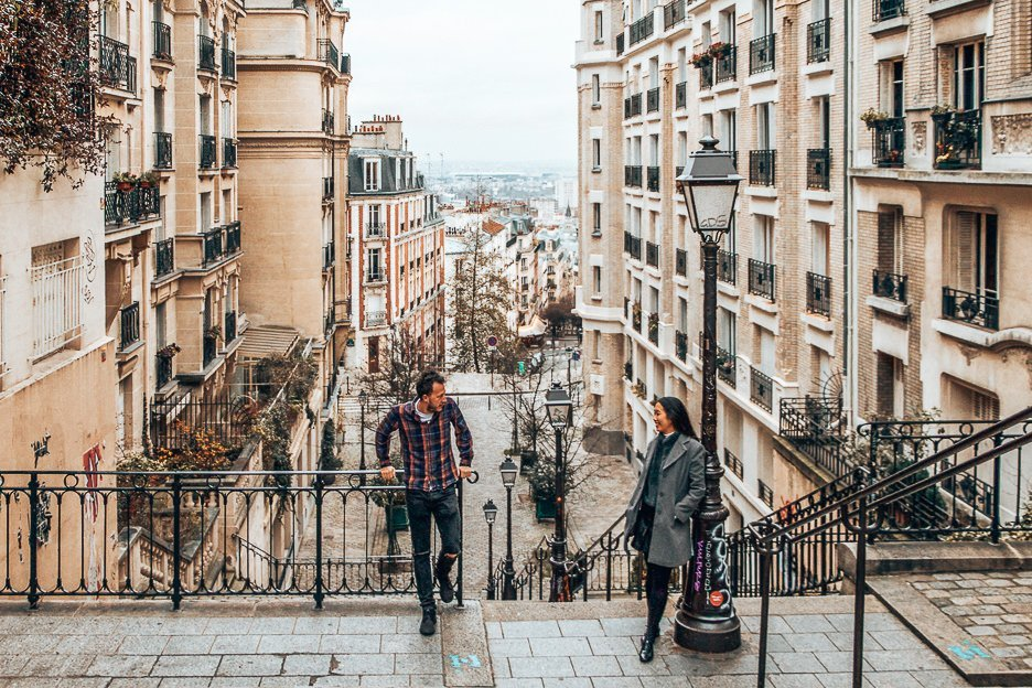 A couple standing at the top of the stairs in Montmartre, Paris - Travelling with Parents