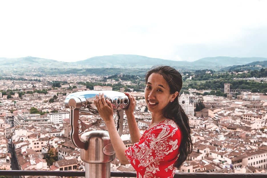 A woman in a red dress smiles at the camera whilst standing next to the binoculars at the top of the Duomo viewing platform over Florence, Italy