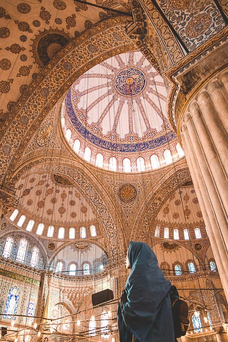 A woman covers her head with a shawl and looks up at the immaculate detail inside The Blue Mosque, Istanbul