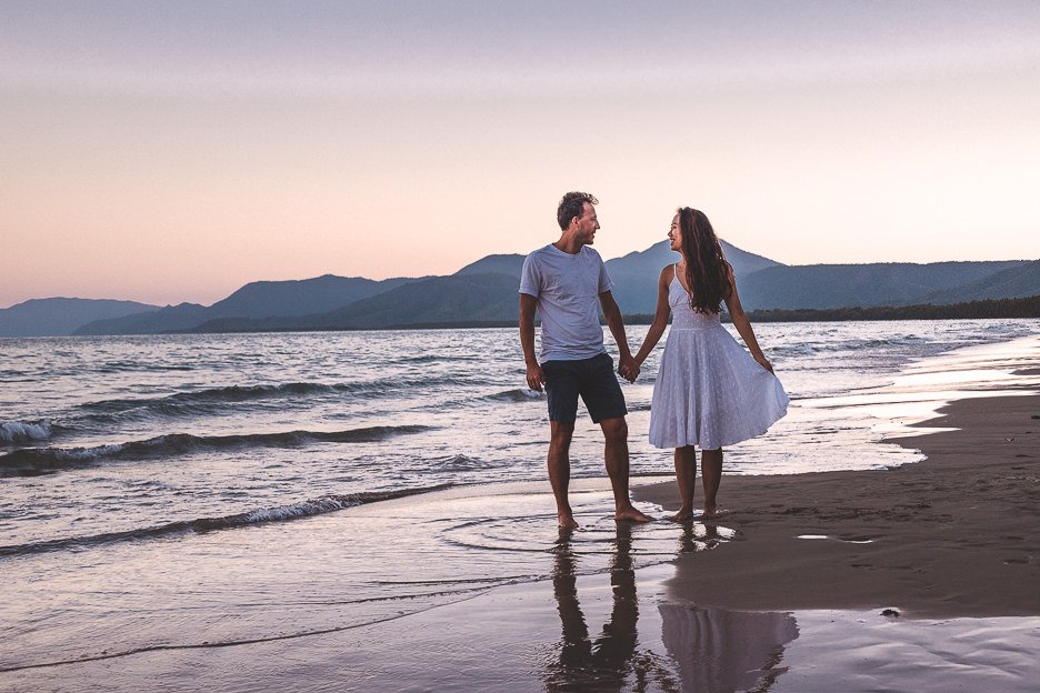 A couple hold hands on Four Mile Beach at sunset in Port Douglas, tropical North Queensland