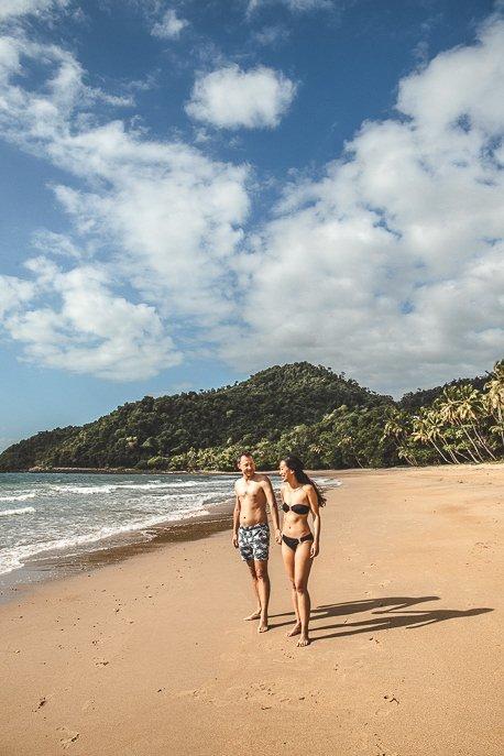 A couple walk along the beach at Bingil Bay, tropical north Queensland