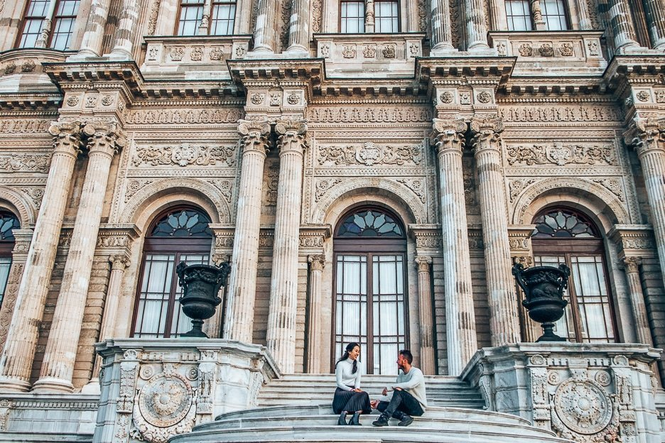 A couple sit on the stairs smiling at each other in front of Dolmabahce Palace in Istanbul, Turkey