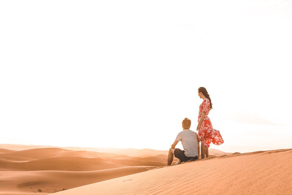 A man sits and a woman stands on a sand dune watching the sunset in the Sahara Desert, Morocco