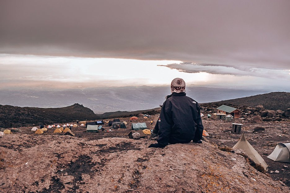Jasmine sitting on a boulder looking over Barranco camp along the Machame Route - 7 days
