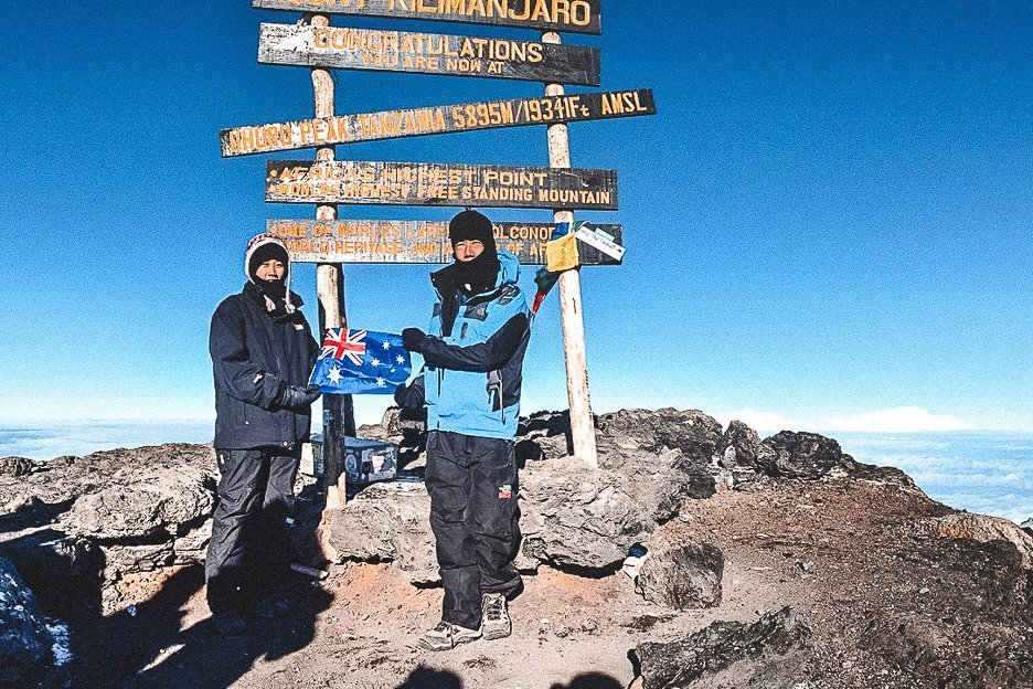 Jasmine standing with her dad holding an Australian flag at the top of Mt Kilimanjaro