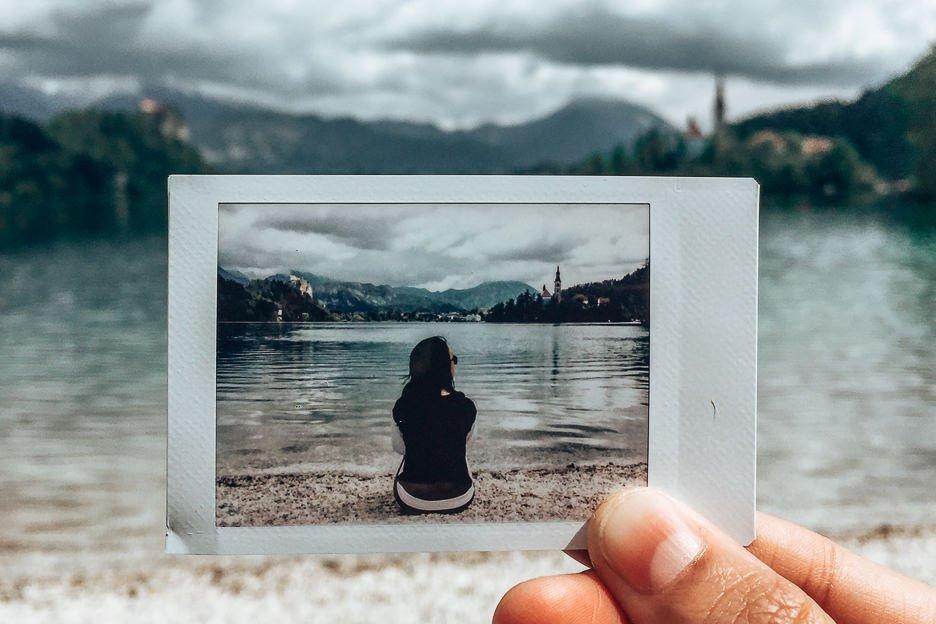 Polaroid snap of Jasmine sitting on the shore of Lake Bled, Slovenia