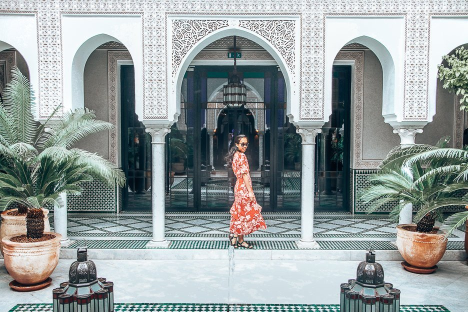 A woman in a red dress twirls in the outdoor courtyard of La Mamounia, Marrakech, Morocco