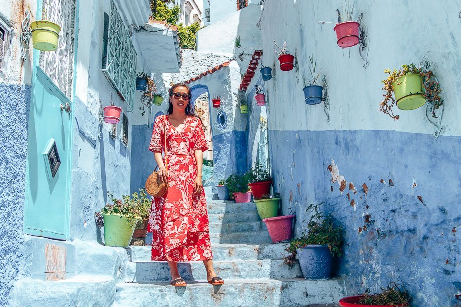 A woman in a red dress poses for a photo on the blue steps of Chefchaouen, Morocco