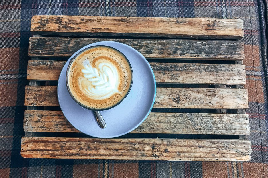 A latte served on a wooden tray at The Milkman, Coffee in Edinburgh Scotland
