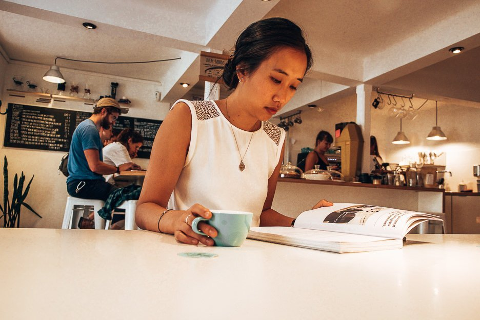 Jasmine reading a magazine and drinking coffee at Copenhagen Coffee Lab, Lisbon Portugal