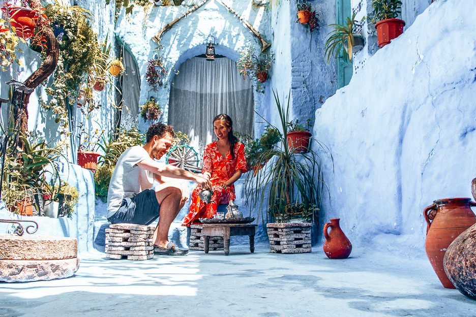 A man and woman sit and pose in a traditional courtyard in Chefchaouen, Morocco