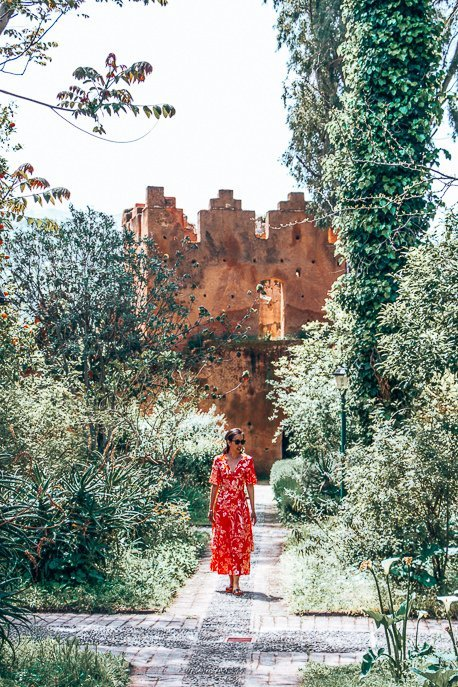A woman in a red dress stands in the garden of the kasbah, Chefchaouen Morocco