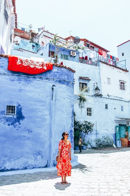A woman wears a red dress standing in front of blue buildings, Chefchaouen Morocco