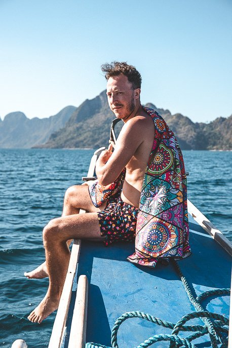 Bevan sits on the edge of the boat with his Tesalate towel, Private Boat Tour in El Nido