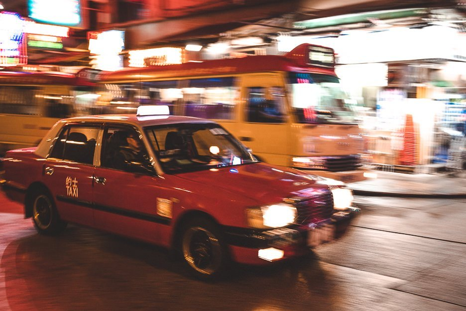 The blur of a red taxi and public light bus in Mong Kok, Hong Kong