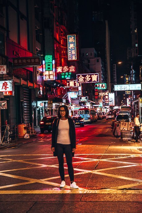 Jasmine standing in the middle of the street with neon lights behind her, Mong Kok