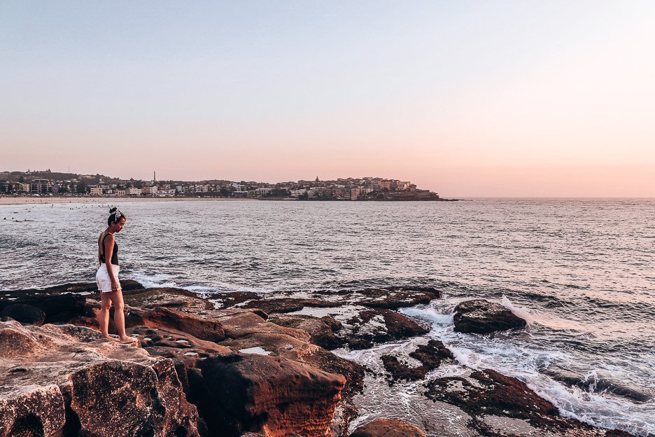 A woman stands on the rocks in Bondi Beach during sunrise