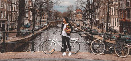 A girl holds a bunch of tulips standing next to her bicycle alongside a canal in Amsterdam, the Netherlands