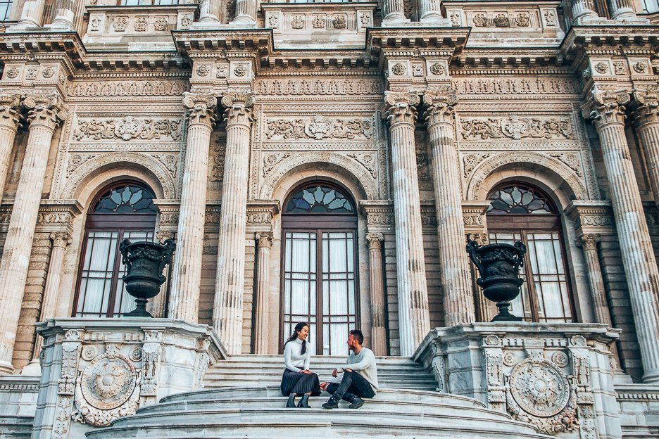 A couple sit on the stairs in front ofDolmabahçePalace in Istanbul, Turkey
