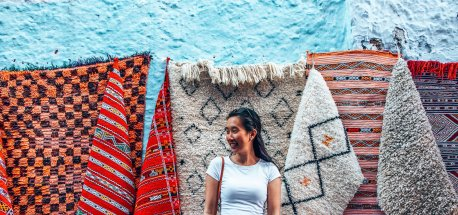 A girl poses in front of rugs for sale in Chefchaouen, Morocco