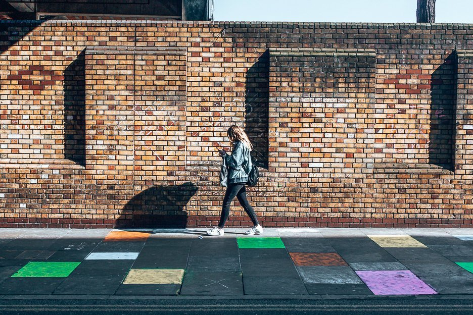 A girl with a denim jackets busy on her phone walking past a hopscotch game in East London, close to Brick Lane