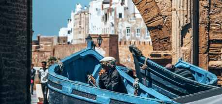 Old fisherman people watching in Essaouira's harbour front, Morocco