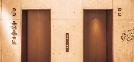 The brass elevator doors at reception at The Lively Azabujuban - Minato City Tokyo