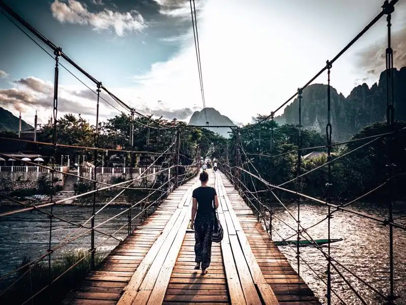 Picture of girl crossing Nam Song bamboo bridge to Vang Vieng viewpoint Laos