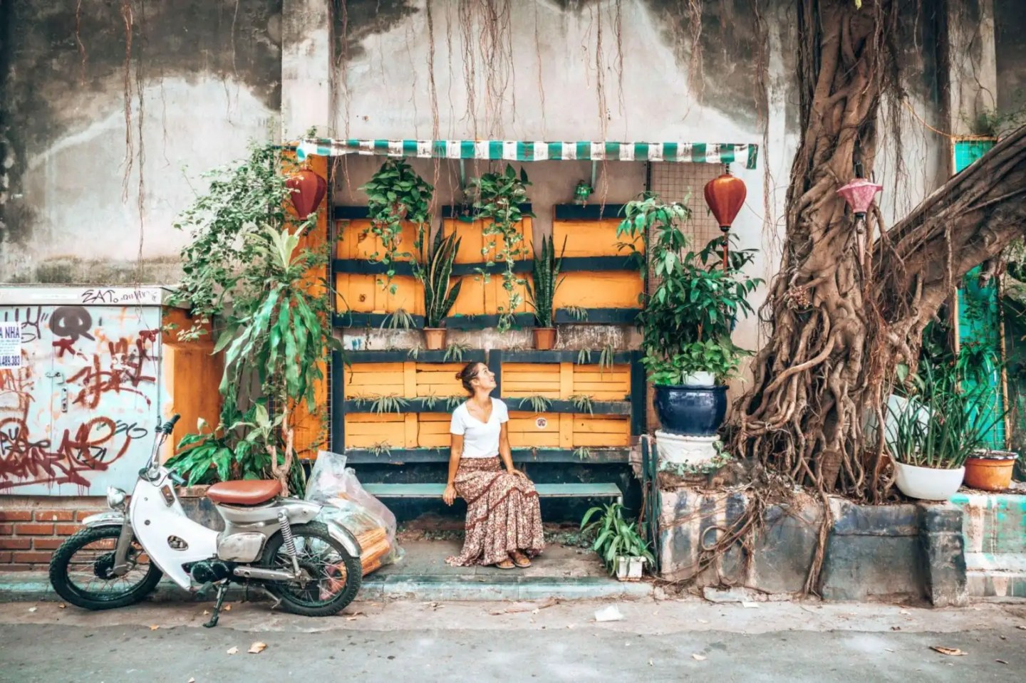 Picture of girl sitting at a photo wall in Hanoi Vietnam