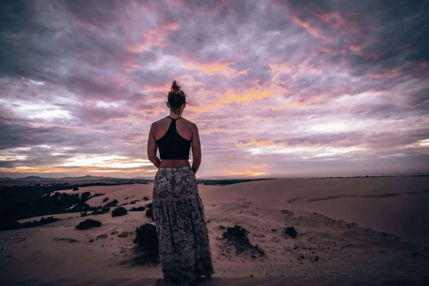 Girl looking out at white sand dunes in Mui Ne, at sunrise