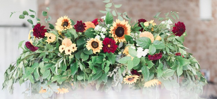 wedding floral arrangement sunflowers red greens donate