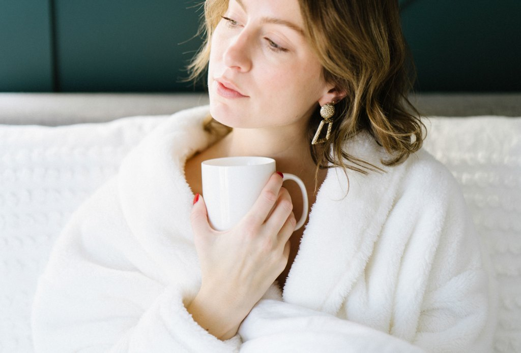 The power of positive thinking. A woman in a robe looks pensively into the distance whilst enjoying a cup of coffee