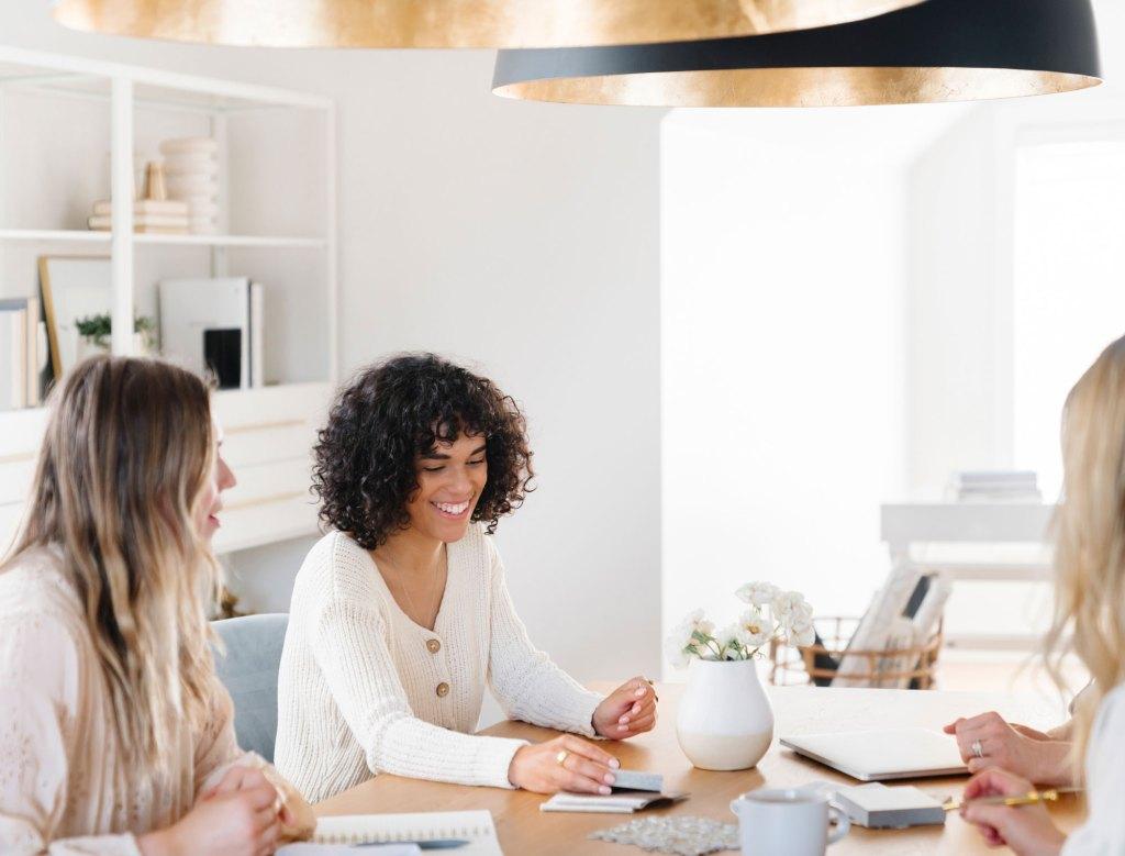 Benefits of coworking. Three  women sat around a desk smiling.