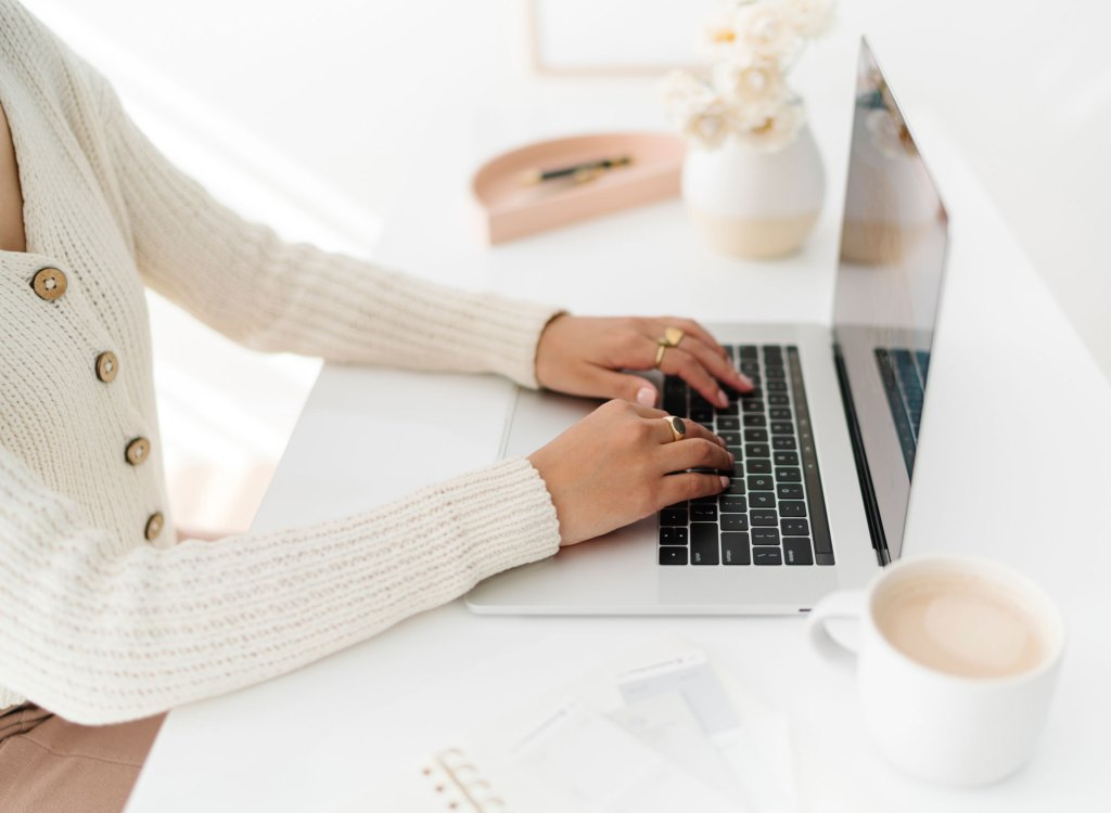 Woman sat at a desk typing on a laptop. Overcoming perfectionism.