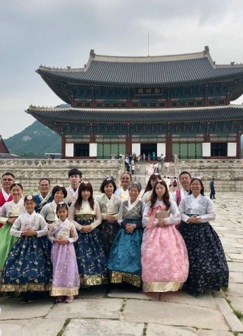 A group of tourists poses in period costume in front of a building in Gyeongbokung Palace, which was the filming site for several K-dramas.