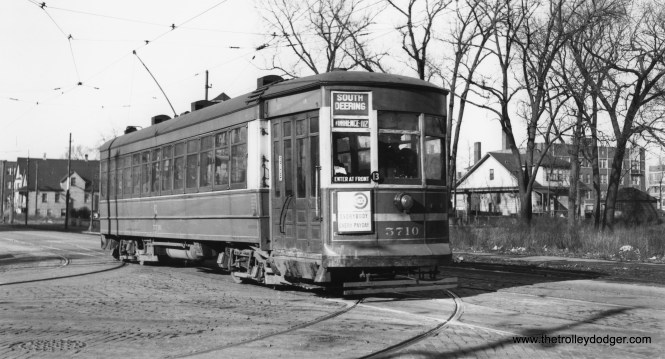"""CSL 5710. Andre Kristopans says, """"SB on Coles at 79th. Tracks curving to left were used by Windsor Park cars, 5710 will curve onto 79th to the right. Note that buildings on South Shore, a block to the right, are large brick apartment buildings, while the buildings on Coles are small wooden houses."""" (Joe L. Diaz Photo)"""